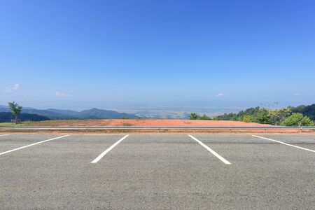 Empty parking lot against mountains and beautiful blue sky.