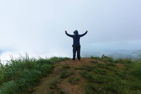 Man traveler on cliff with beautiful foggy in national park.