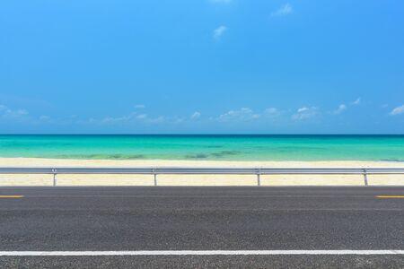 Side view of asphalt road with sea and beautiful blue sky. 版權商用圖片