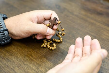 Closeup of catholic rosary beads in hand on wooden table.