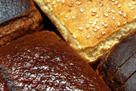boodle: three loaves of black and loaf of wheat bread Stock Photo
