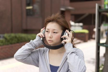 Young woman in headphone. Asian woman photo