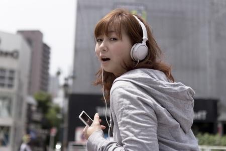 ヘッドフォンで、若い女性。アジアの女性