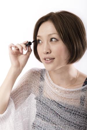 Bautiful asian woman applying mascara Stock Photo - 10524620