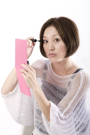 Bautiful asian woman applying mascara Stock Photo - 10524618