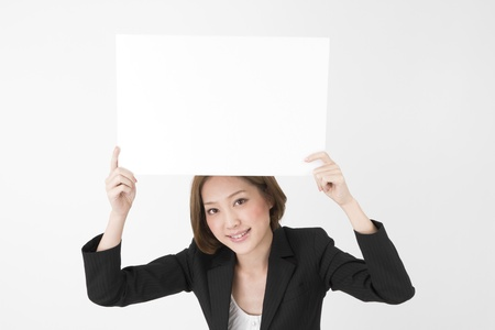 美しいアジア ビジネスの女性が、ホワイト ボードを保持しています。