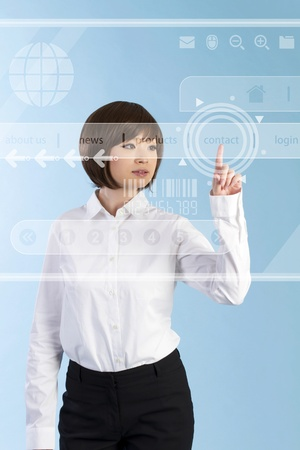 Beautiful business woman pushing touch screen.  photo