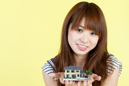 Beautiful young woman with house model photo
