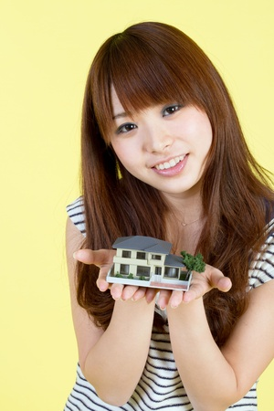 Beautiful young woman with house model Stock Photo - 11957261