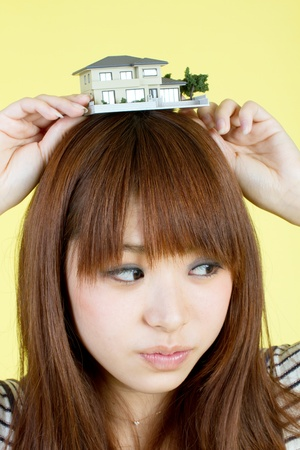Beautiful young woman with house model Stock Photo - 11957311