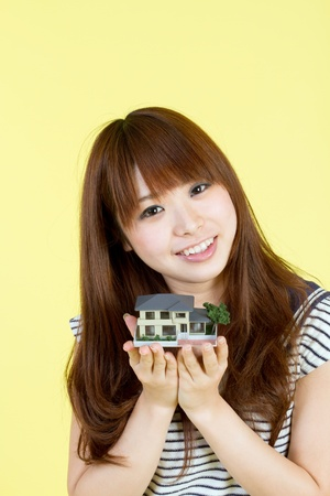 Beautiful young woman with house model Stock Photo - 11957262