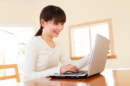 Beautiful asian woman using a laptop computer Stock Photo - 12012907