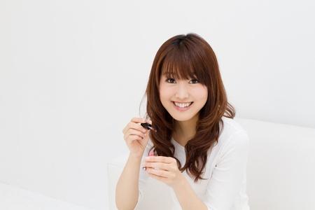 彼女の爪を描く美しいアジアの女性