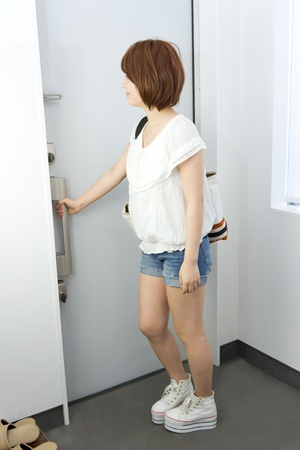 out of doors: Beautiful young woman opening door  Portrait of asian woman