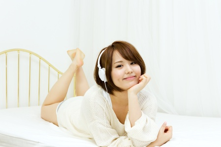 Beautiful young woman relaxing in the bedroom 스톡 콘텐츠