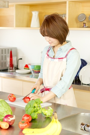 Beautiful young woman in kitchen making salad photo