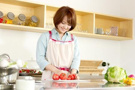 サラダを作る台所で美しい若い女性