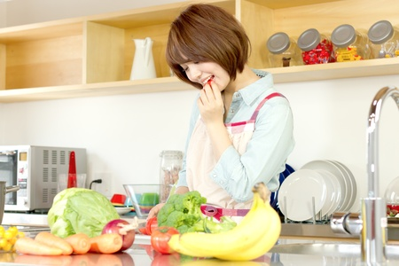 Beautiful young woman in kitchen making salad