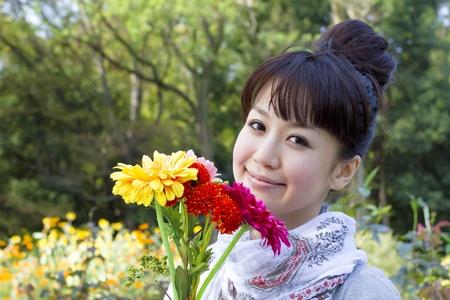 briskness: Beautiful asian woman in flower garden  Stock Photo