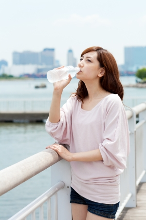 Beautiful young woman drinking water photo