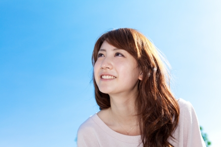 Beautiful young woman outdoors over blue sky  Portrait of asian photo