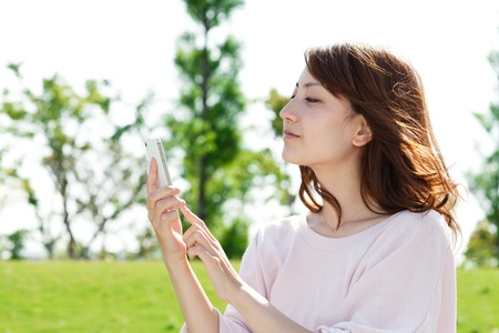 Beautiful young woman using a moblie phone in a park photo