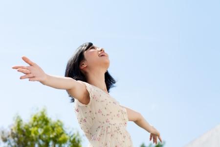 青い空に屋外の美しい若い女性