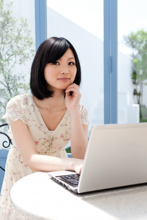 Beautiful young woman using a laptop computer photo