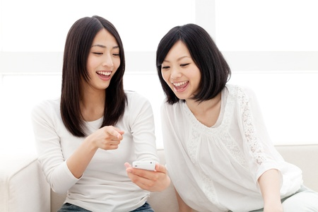 korean fashion: Beautiful young women using a moblie phone  Portrait of asian women   Stock Photo