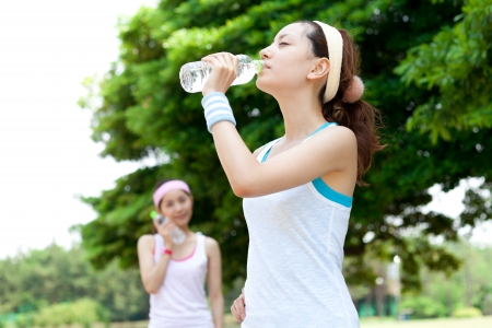 sport wear: Beautiful young women drinking water at workout  Portrait of asian Stock Photo