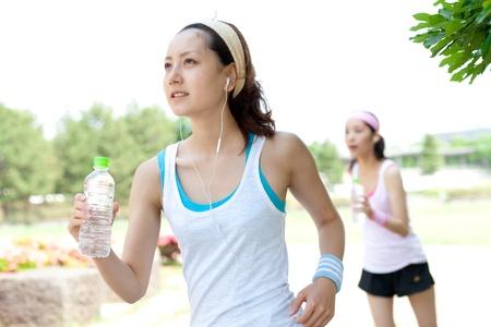 アジアの肖像画の公園で走っている美しい若い女性