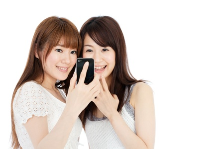 Beautiful young women using a mobile phone Stock Photo - 14201807