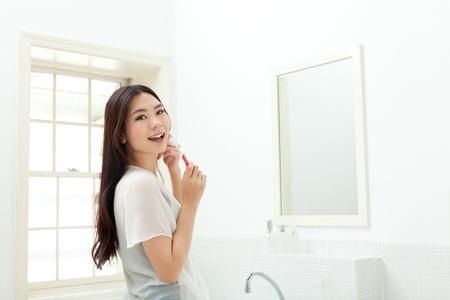 Beautiful young woman brush her teeth in the bathroom photo