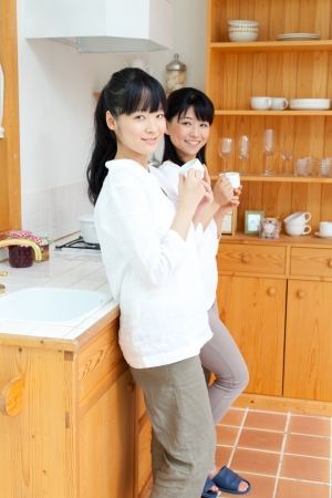 Beautiful young women relaxing in the kitchen photo