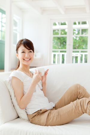 Mooie jonge vrouw ontspannen in de kamer Stockfoto