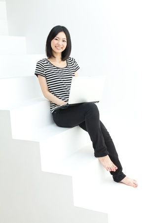 Beautiful young woman using a laptop computer  Portrait of asian