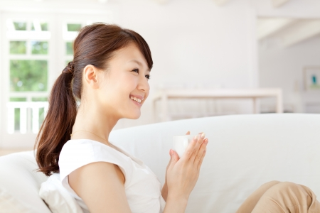 chinese drinks: Beautiful young woman relaxing in the room Stock Photo