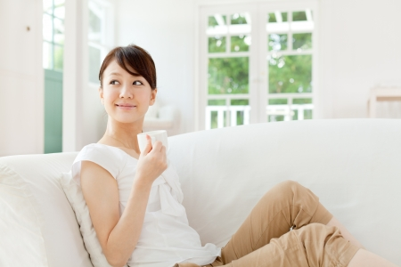 attractive couch: Beautiful young woman relaxing in the room Stock Photo