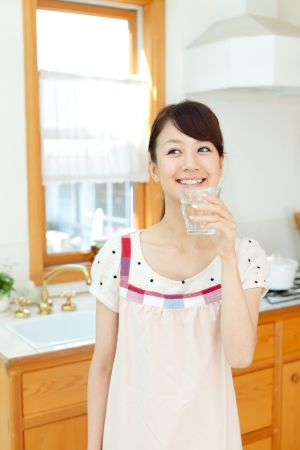 Beautiful young woman in the kitchen photo