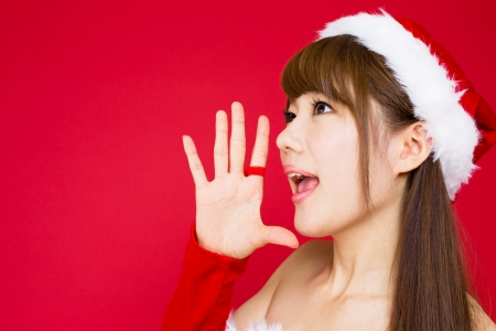 Beautiful asian woman in santa hat excited for Christmas on red photo