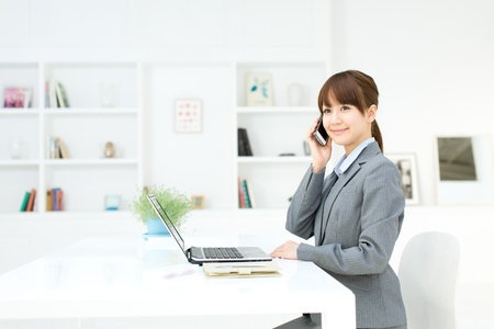 office workers: Beautiful young businesswoman working in office