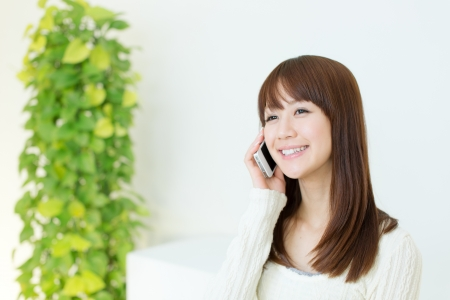 Beautiful young woman using a cellular phone Stock Photo - 17539917