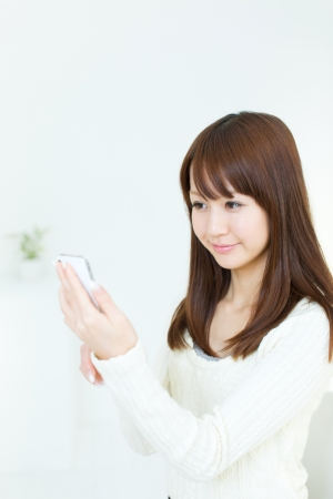 Beautiful young woman using a cellular phone Stock Photo - 17539912