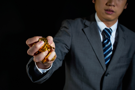 invest: Businessman holding gold coins isolated on black
