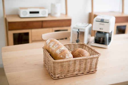 mimbre: Fresh french bread in basket over white wooden table with copy space