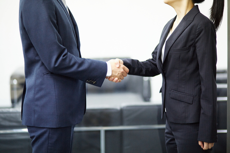 two men: Two business people shaking hands