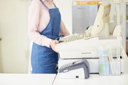 Jeune caissière aidant un salaire à la clientèle Banque d'images