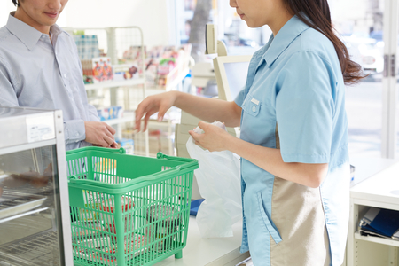 convenient store: Young female cashier helping a customer pay Stock Photo