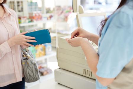 Jeune caissière aidant un salaire à la clientèle