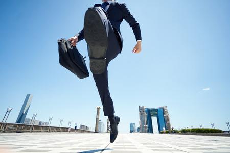 ビジネスの男性が道路上でジャンプ